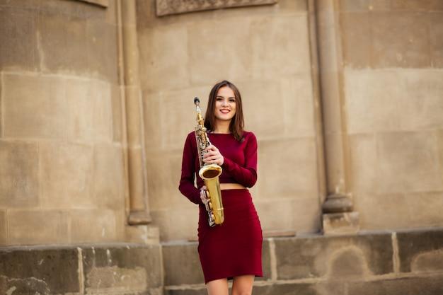 Beleza e moda, música. linda mulher com saxofone.