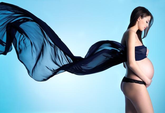 Beleza e sensualidade de uma jovem grávida com um material azul - espaço azul