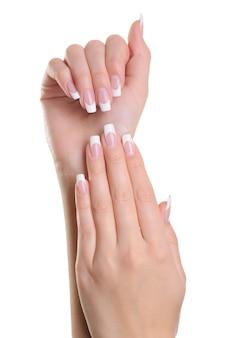 Beleza elegante com mãos de mulher com manicure francesa isolada no branco