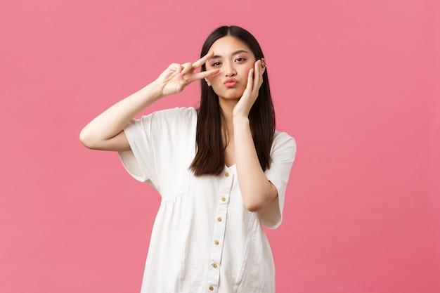 Beleza, emoções das pessoas e conceito de lazer de verão. menina asiática bonita e elegante em um vestido branco, posando com o símbolo da paz kawaii, tocando seu rosto bonito, fundo rosa de pé.