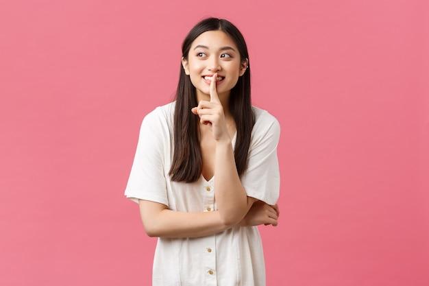 Beleza, emoções das pessoas e conceito de lazer de verão. sonhadora e fofa, adorável garota asiática se calando, pedindo pra ficar quieta ou não contar seu segredo pra ninguém, desviando o olhar e sorrindo enquanto fofocava.