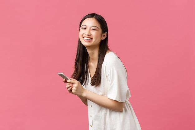 Beleza, emoções das pessoas e conceito de tecnologia. despreocupada feliz, terna menina asiática em um vestido branco, segurando o smartphone e lauhing para a câmera, lendo uma história engraçada no feed do telefone móvel, fundo rosa.