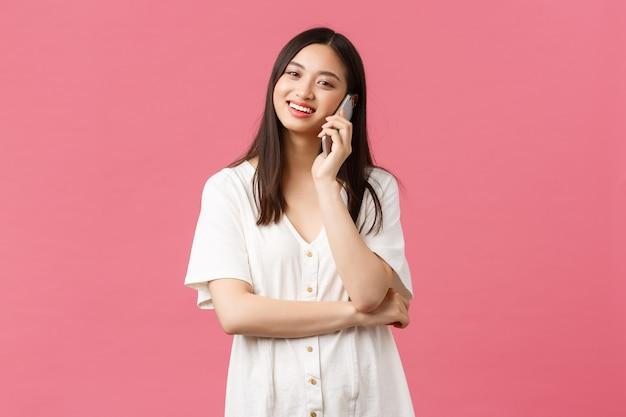 Beleza, emoções das pessoas e conceito de tecnologia. feliz menina asiática em vestido branco falando no telefone, segurando o celular e olhando a câmera, chamando o amigo, fundo rosa.