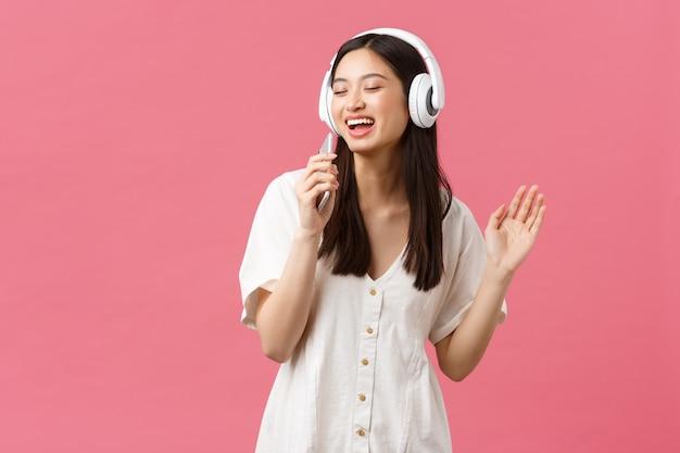 Beleza, emoções das pessoas e conceito de tecnologia. menina asiática feliz despreocupada usando aplicativo de karaokê para celular, cantando no microfone do smartphone, ouvindo música em fones de ouvido, fundo rosa