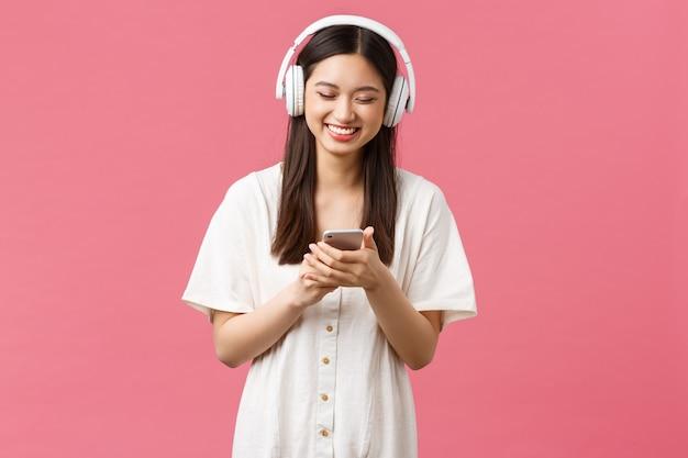 Beleza, emoções das pessoas e conceito de tecnologia. menina asiática sorridente e despreocupada curtindo música ou podcast engraçado em fones de ouvido sem fio, usando o aplicativo de streaming para celular