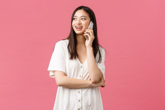 Beleza, emoções das pessoas e conceito de tecnologia. menina bonita sorridente amigável no vestido branco falando no telefone feliz, olhando para cima e em pé fundo rosa alegre.