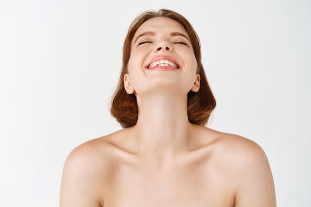 Beleza facial. menina natural com pele limpa e saudável, ombros nus, rindo e sorrindo despreocupada. mulher livre desfrutando de uma sensação de frescor e limpeza no rosto, parede branca