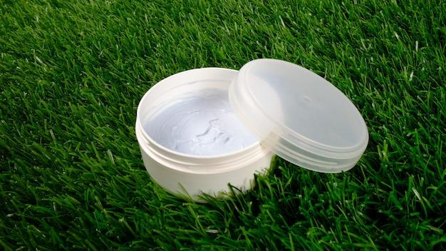 Beleza, frasco branco com esfoliante corporal em close-up de grama verde. cosméticos para os cuidados da pele.
