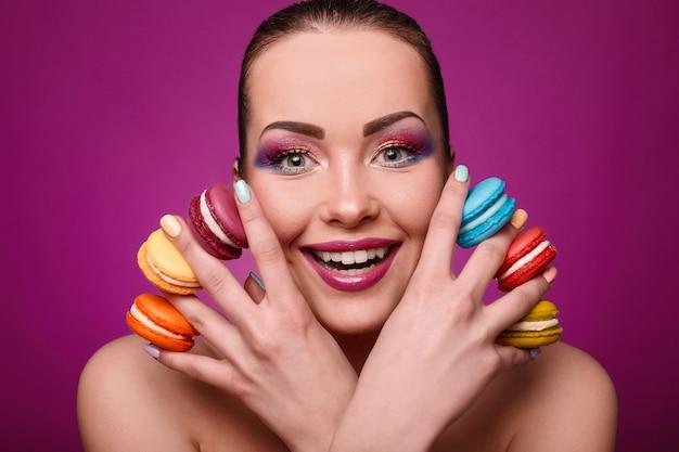 Beleza glamour moda modelo garota com maquiagem colorida e biscoitos.