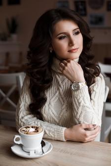 Beleza incrível mágica de uma jovem sentada no café com uma xícara de café e olhando pela janela. sonhos de morena. lindo cabelo ondulado, maquiagem luxuosa. decorado com café art.
