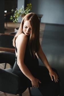 Beleza incrível, uma jovem grávida em um vestido preto da moda está sentada na cadeira no escuro em ...