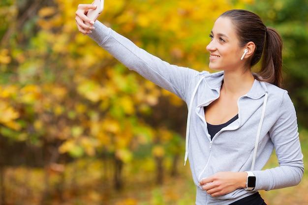 Beleza jovem, com longos cabelos castanhos, olhando para smartphone tirando foto de si mesma