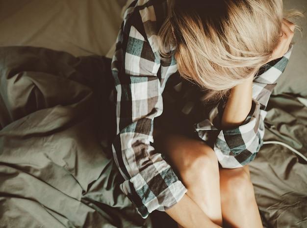 Beleza jovem feminina em uma camisa casual na cama