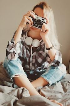 Beleza jovem feminina em uma camisa casual tirando uma foto com sua câmera vintage sentada em uma cama