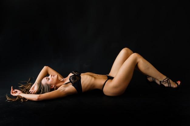 Beleza jovem perfeita em lingerie preta sedutora e meias, estúdio tiro