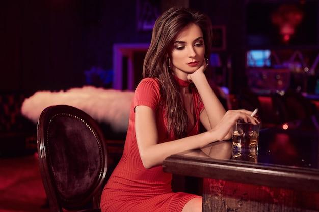 Beleza linda jovem morena de vestido vermelho com cigarro e uísque