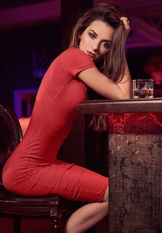 Beleza linda jovem morena de vestido vermelho com um copo de uísque