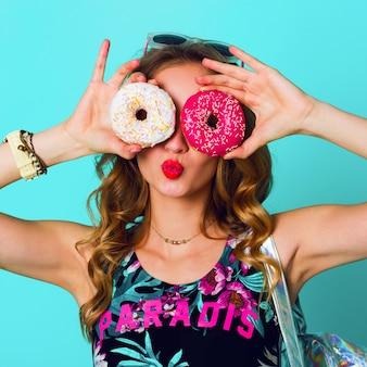 Beleza loira moda modelo garota tomando rosquinhas rosa coloridas. mulher alegre engraçada com doces, sobremesa. dieta, conceito de dieta. comida não saudável. cores brilhantes.