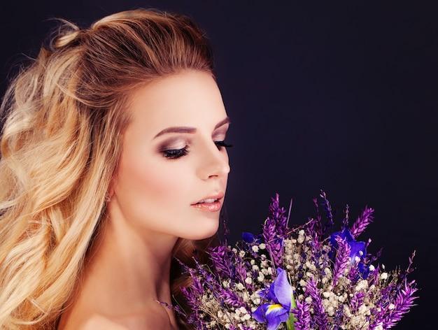 Beleza loira. mulher perfeita com flores roxas