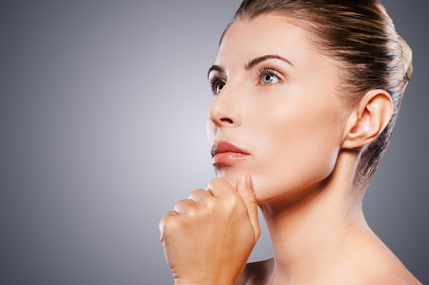 Beleza madura pensativa. vista lateral de uma mulher madura pensativa, segurando a mão no queixo e desviando o olhar enquanto está de pé contra um fundo cinza