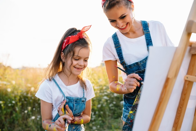 Beleza mãe pintura com sua filha. mulher elegante desenhando com a garotinha. gracinha em uma camiseta branca e calça jeans azul.
