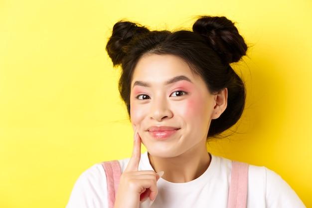 Beleza. menina asiática elegante com maquiagem glamour brilhante, tocando a pele do rosto macia e brilhante, sorrindo feliz para a câmera, parada no amarelo