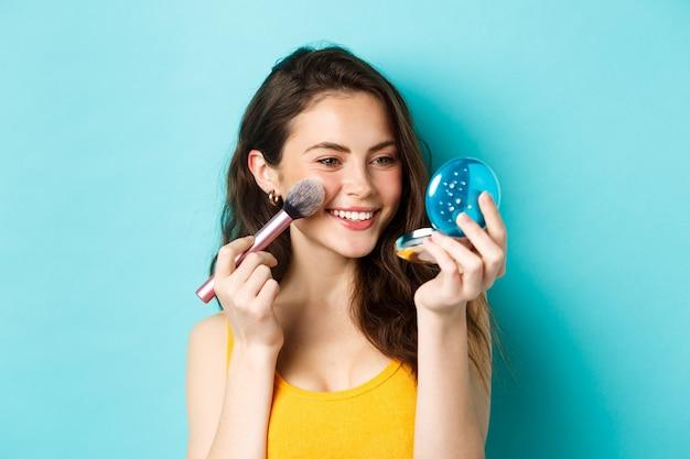 Beleza. menina moderna com sorriso sincero, aplicando maquiagem com pincel, olhando no espelho de bolso, em pé sobre um fundo azul