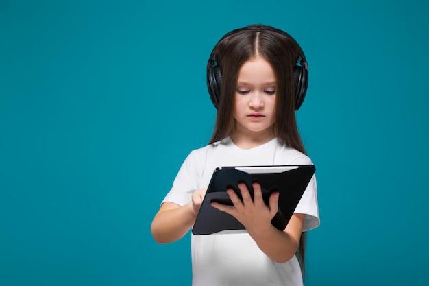Beleza, menininha, em, tee, camisa, e, fones ouvido, com, cabelo longo, segure tabuleta