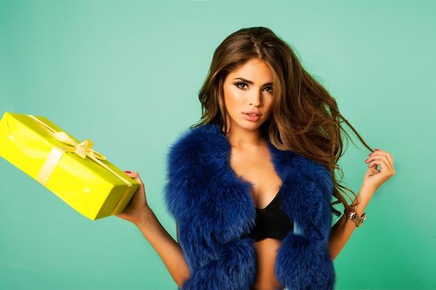 Beleza moda modelo menina com casaco de pele de vison azul. mulher bonita do inverno de luxo. garota hippie louca, impressionada com seu presente