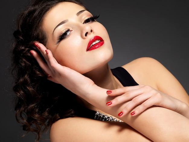 Beleza moda mulher com unhas vermelhas, lábios e maquiagem dourada nos olhos