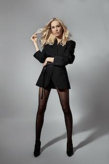 Beleza moda mulher sexy em jaqueta e meia-calça, menina loira com pernas longas. figura perfeita de modelo