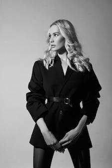 Beleza moda mulher sexy em uma jaqueta e meia-calça, uma menina loira com pernas longas. figura perfeita de um modelo, retrato de uma mulher em uma parede cinza