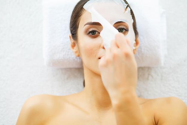 Beleza. mulher bonita no salão de beleza com máscara protetora. deitado nas mesas de massagem. pele pura e fresca. cuidados com a pele. alta resolução