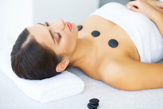 Beleza. mulher bonita no salão de beleza. relaxe e deite-se nas mesas de massagem. pele limpa e fresca. alta resolução