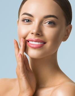 Beleza mulher cuidados com a pele linda mão feminina tocando rosto modelo de menina cosmética sobre fundo azul