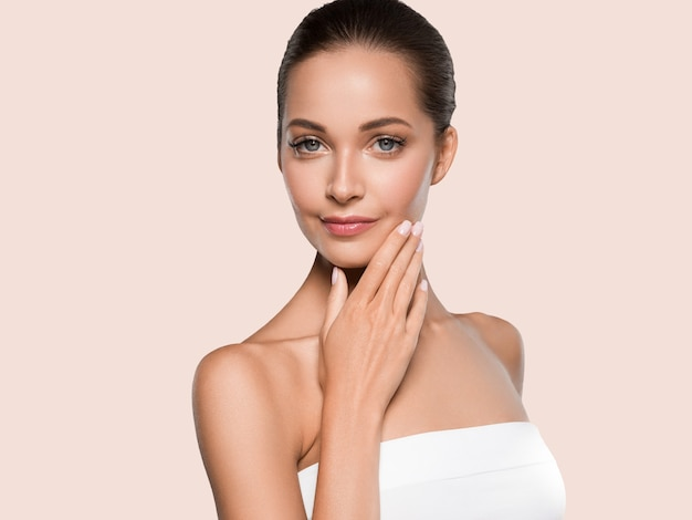 Beleza mulher pele saudável spa manicure limpo unhas mãos tocando o rosto. cor de fundo amarelo