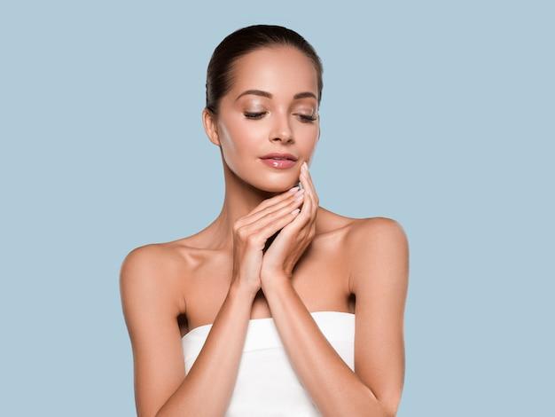 Beleza mulher pele saudável spa manicure limpo unhas mãos tocando o rosto. cor de fundo azul
