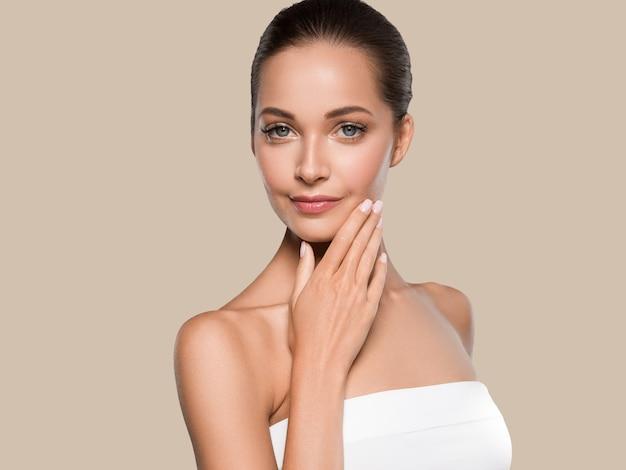 Beleza mulher pele saudável spa manicure limpo unhas mãos tocando o rosto. cor de fundo marrom