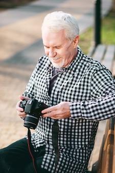 Beleza nas fotos. vista superior de um homem maduro meditando, usando a câmera e sentado no banco