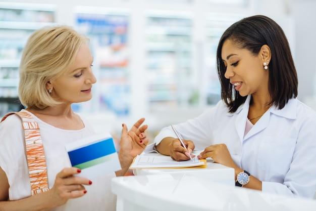 Beleza natural. cliente maduro fofo segurando pacote com remédio na mão direita enquanto verifica o certificado