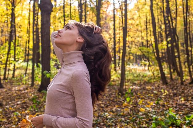 Beleza natural com uma bela mulher no parque outono