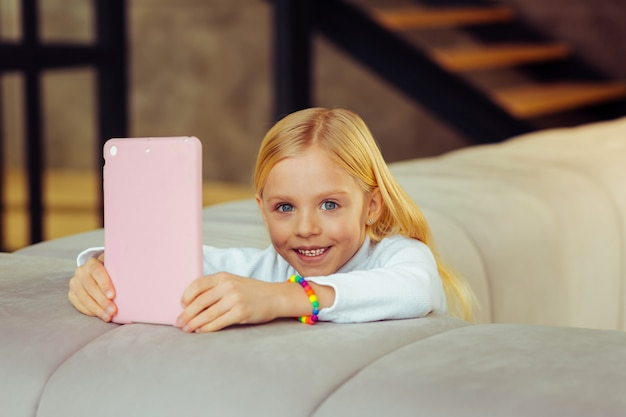 Beleza natural. criança de cabelos compridos com um sorriso no rosto enquanto passa o fim de semana em casa