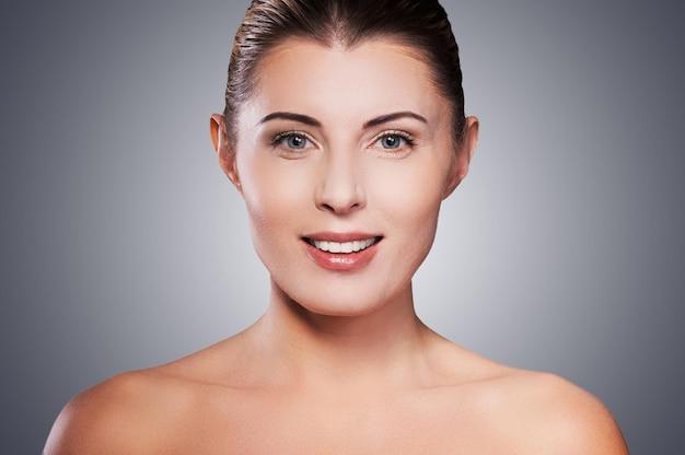 Beleza natural. retrato de mulher madura sem camisa sorrindo em pé contra um fundo cinza
