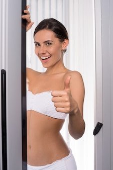 Beleza no solário. mulher jovem e atraente olhando para fora da cabine de bronzeamento e gesticulando