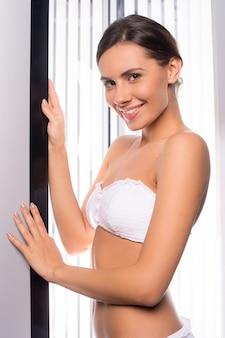 Beleza no solário. mulher jovem e bonita em pé na cabine de bronzeamento e sorrindo para a câmera