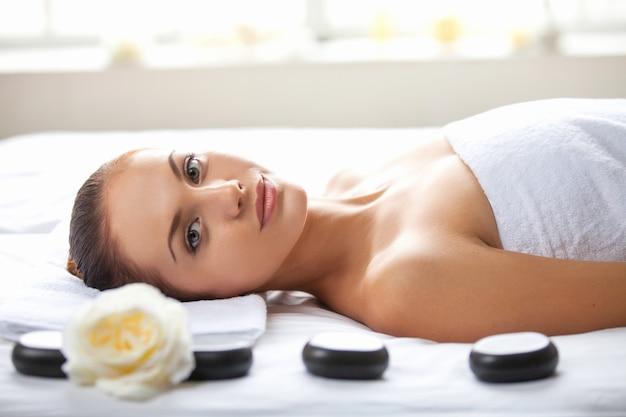Beleza no spa. mulher jovem e bonita deitada na mesa de massagem e olhando para a câmera