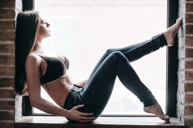 Beleza relaxada. vista lateral de uma bela jovem de jeans e sutiã, mantendo os olhos fechados enquanto está sentada no parapeito da janela