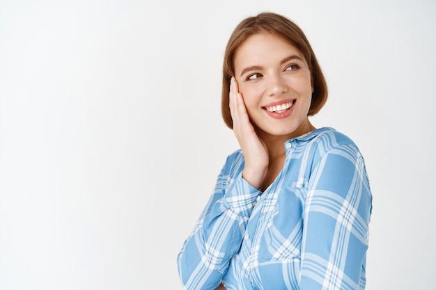 Beleza. retrato de mulher feliz tocando a bochecha e olhando de lado no espaço vazio. rapariga com pouca maquilhagem natural, pele saudável e perfeita após cosméticos de cuidados diários, parede branca