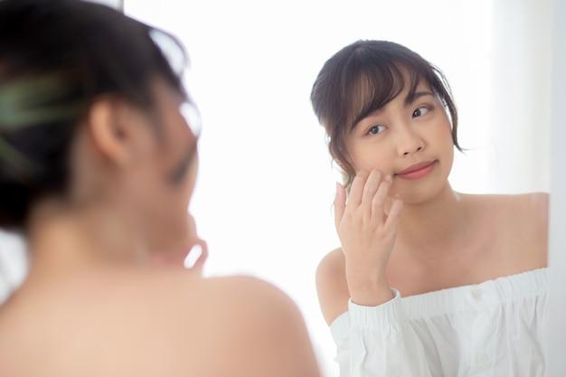 Beleza retrato jovem mulher asiática sorrindo olhar espelho de verificação de cuidados com a pele
