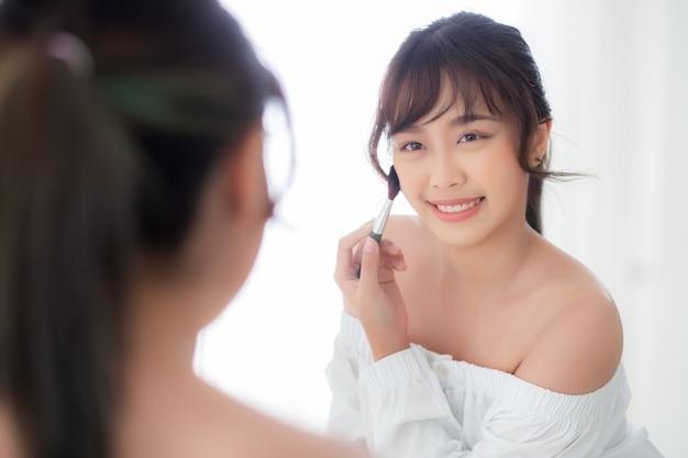 Beleza retrato jovem mulher asiática sorriso com rosto olhando espelho aplicar maquiagem